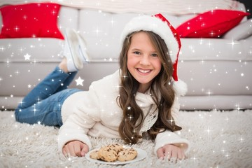 Composite image of festive little girl eating cookies