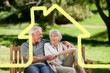 Composite image of senior couple sitting on a bench