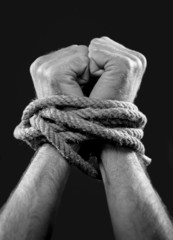 white man hands wrapped rope around wrists victim abused concept