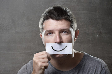 young depressed man lost in sadness holding paper smiley