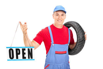 Young male mechanic holding open sign
