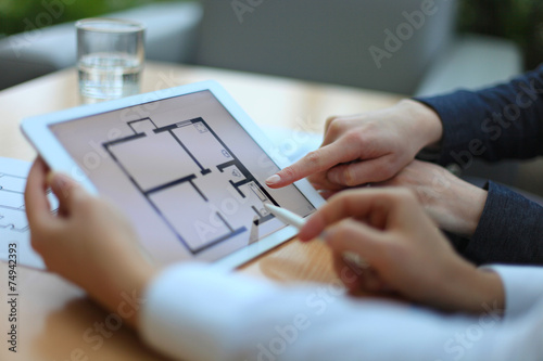 Real-estate agent showing house plans on electronic tablet - 74942393