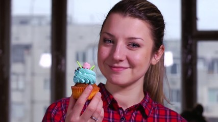 Pastry girl shows cupcake for dessert