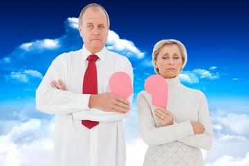 Composite image of older couple standing holding broken pink hea