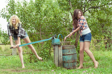 Blonde and brunette throwing water over each other