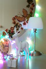 Белая фигурка оленя на комоде на фоне гирлянд