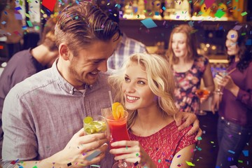 Composite image of happy couple drinking cocktails together