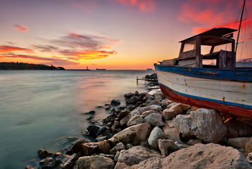 Sunset view with an old boat at the Black sea coast