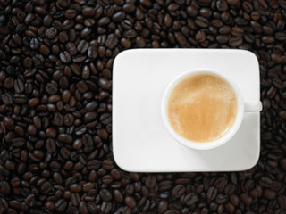 A cup of cafe latte with coffee beans