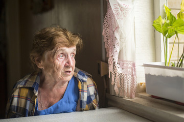 Old woman alone near a window in his country house.