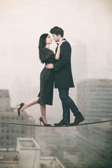 Couple in love standing on a rope over the city