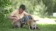 Young man playing with dogs in the park