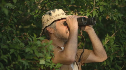 Man with binoculars in the forest