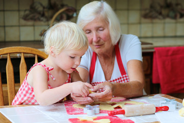 Grandma and granddaughter making cookies together