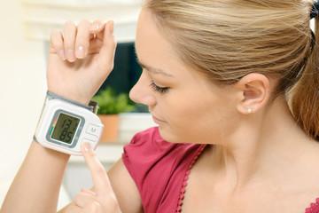 Frau misst Blutdruck mit Messgerät