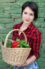 Young woman with a basket of peppers