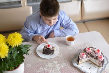 Boy eating cake at  table