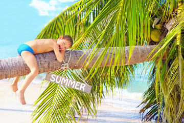 happy kid relaxing on coconut palm on the beach