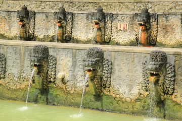 Row of dragon fountains at hot springs in Bali, Indonesia