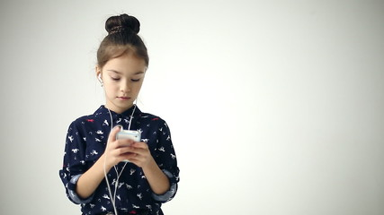 Child uses smartphone with headphones at background