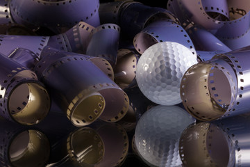 Close-up of a roll 35 mm photographic films and golf ball