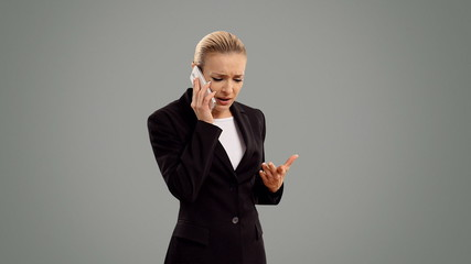 Young blond businesswoman speak for phone on grey background