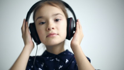 Child with headphones dancing at studio background