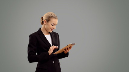 Young blond businesswoman speak with a tablet on grey background