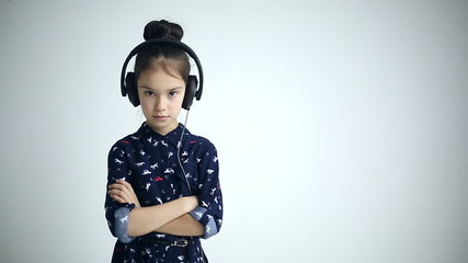 Child with headphones standing at studio background