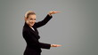 Young  blond businesswoman crosses his arms  on grey background