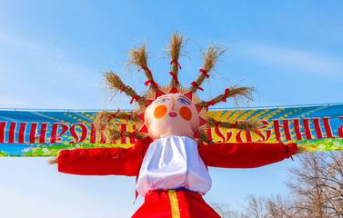 Shrovetide in Russia. Big doll for the burning on blue sky backg