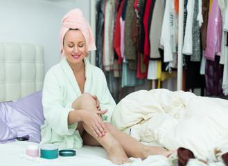 Woman on bed rubbing cream into skin