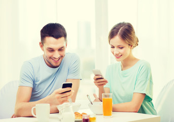 smiling couple with smartphones reading news