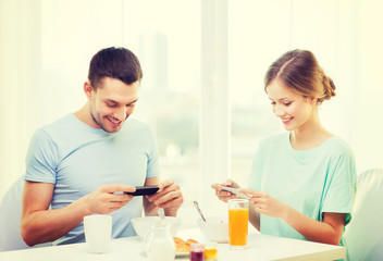 smiling couple with smartphones taking picture