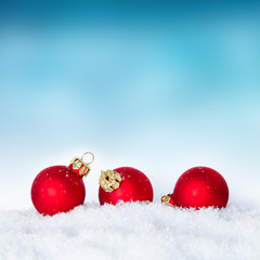 red balls of xmas time and snow with blue wall space