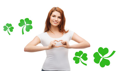 smiling girl showing heart gesture with shamrock