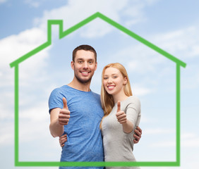 smiling couple showing thumbs up over green house