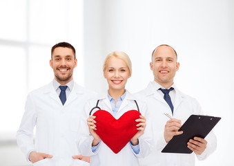 group of smiling doctors with heart and clipboard