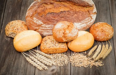 Brotlaib mit Brötchen und Getreideähren auf Holztisch