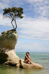 Woman seats on an isolated rock, Abel Tasman Park, New Zealand