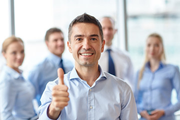 smiling business team showing thumbs up in office