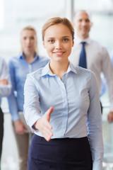 smiling businesswoman making handshake in office
