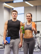 happy couple in gym with water and tablet pc