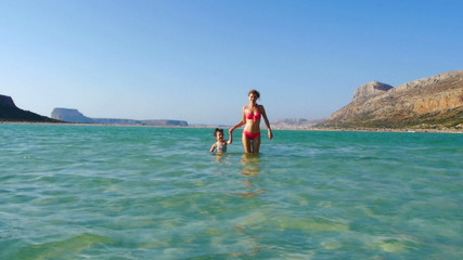 Mother and daughter walking in the sea