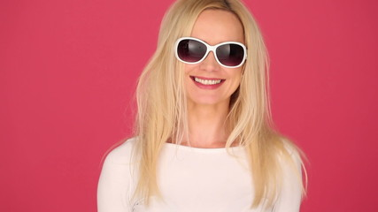 Vivacious young blond woman in trendy sunglasses