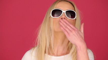 woman wearing sunglasses sending a kiss