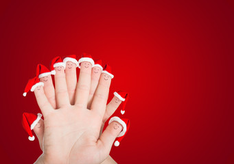 Fingers faces in Santa hats against red. Holiday concept for Chr