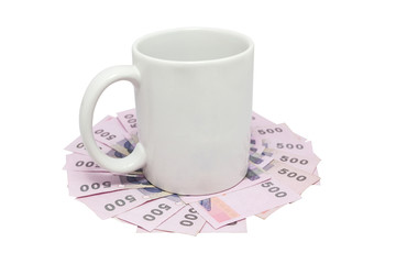White mug over thai money isolated on white with clipping path