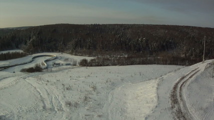 View from above of snow-covered field and forest