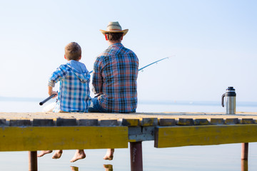 boy and his father fishing togethe
